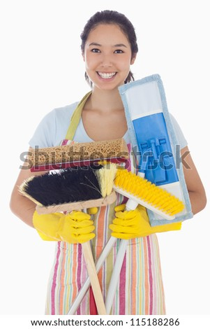 Woman in apron and rubber gloves holding mops and brushes - stock photo