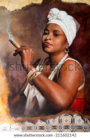 Woman in Aruba wearing a head scarf and traditional jewellery smoking a big fat Cuban cigar with a look of relish and defiance against an old grunge graffiti painted brown wall - stock photo