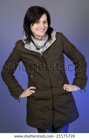 Woman in autumn/winter clothes posing in studio and smiling - stock photo