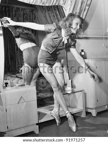 Woman in ballerina shoes dancing in front of a mirror