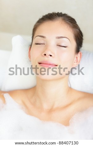 Woman in bath relaxing. Closeup of young asian woman in bathtub bathing with closed eyes. - stock photo