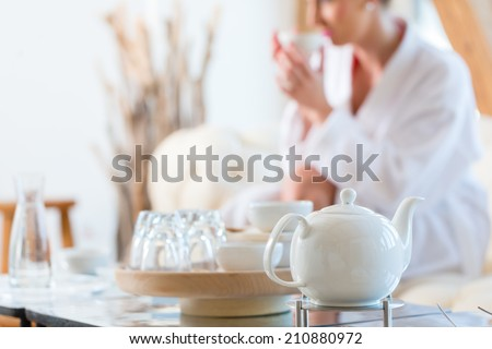 Woman in bath robe drinking tea in wellness spa relaxation room - stock photo