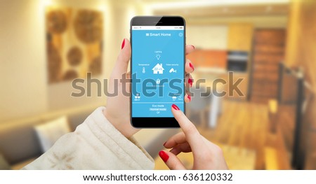 Woman in bathrobe holding phone with smart house system app, living room background