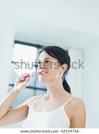 woman in bathroom brushing teeth. Copy space - stock photo
