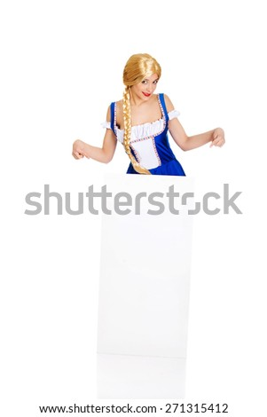 Woman in Bavarian dress pointing on empty banner. - stock photo