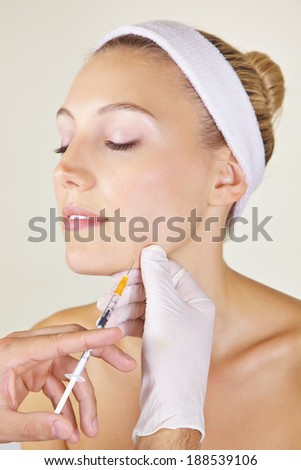 Woman in beauty clinic getting cosmetic surgery with syringe - stock photo
