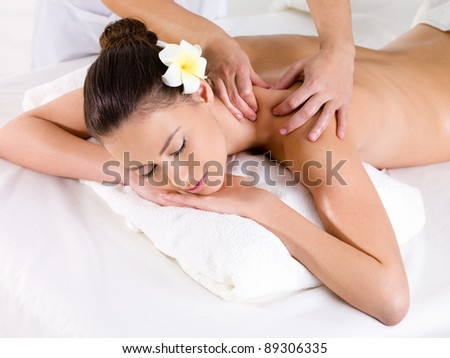 Woman in beauty salon having massage of shoulder   - horizontal - stock photo
