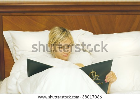 Woman in bed in hotel choosing from the menu - stock photo