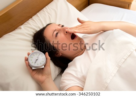 woman in bed yawning with alarm clock in hand - stock photo