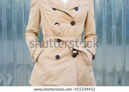 Woman in beige coat outdoors closeup - stock photo