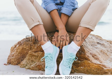 Woman in beige pants and a denim shirt and turquoise sneakers sitting on a rock by the sea. Shirt sleeves rolled up, watch on her arm, a blue manicure. Closeup. - stock photo