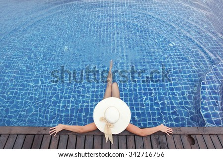Woman in big hat relaxing in swimming pool - stock photo