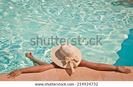 Woman in big summer straw hat relaxing on the swimming pool. Girl at travel spa resort pool. Summer luxury vacation. - stock photo