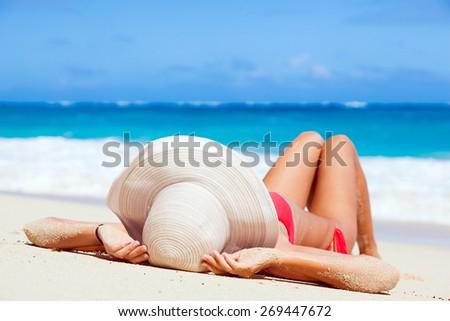 woman in bikini and straw hat lying on tropical beach - stock photo