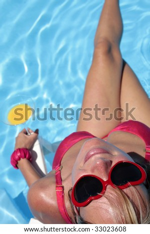 Woman in bikini and suglasses with cocktail and nice blue pool background - stock photo