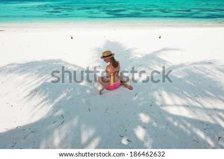Woman in bikini at tropical beach under the palm tree shadow - stock photo
