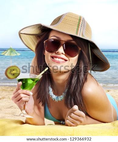 Woman in bikini drinking alcohol cocktail through  straw. - stock photo