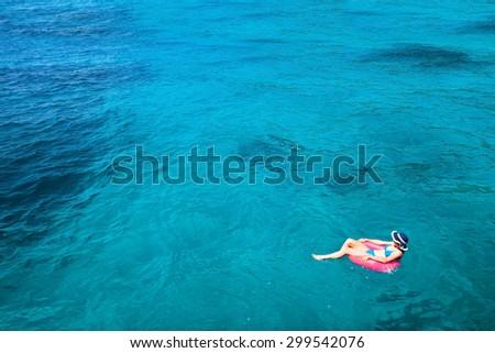woman in bikini enjoying turquoise sea on paradise beach, background with copyspace - stock photo