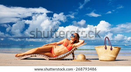 Woman in bikini lying on tropical beach at Seychelles - stock photo