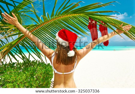 Woman in bikini on a tropical beach at christmas - stock photo