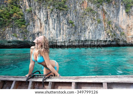 Woman in bikini on boat floating in beautiful lagoon in Thailand - stock photo