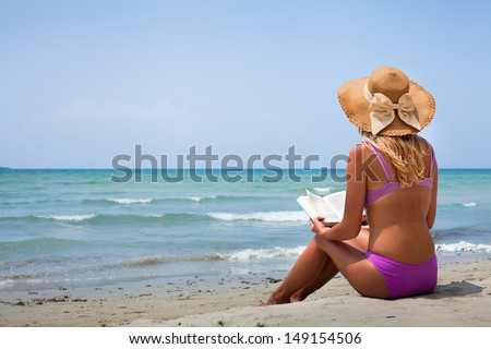 woman in bikini reading book on the beach - stock photo