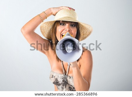 Woman in bikini shouting by megaphone over textured background