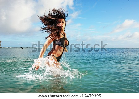 woman in bikini splashing in ocean - stock photo
