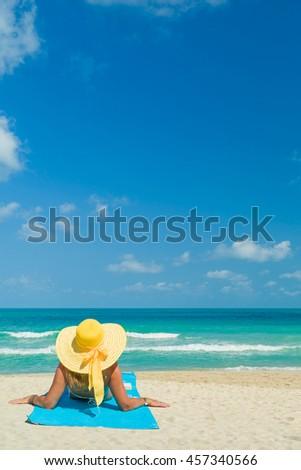 Woman in bikini wearing a yellow hat suntanning at tropical beach - stock photo
