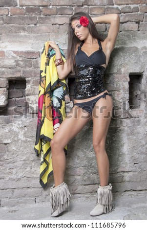 woman in bikini with a scarf against the wall of red brick - stock photo