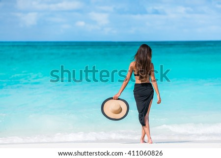 Woman in black bikini and sarong standing on beach. Elegant sexy female is wearing black bikini and sarong on beach. Woman is holding sunhat enjoying her summer vacation at resort in the Caribbean. - stock photo