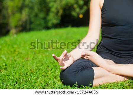 woman in black clothes practicing yoga outside, on a grass