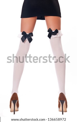 woman in black dress and white stockings on an isolated background - stock photo