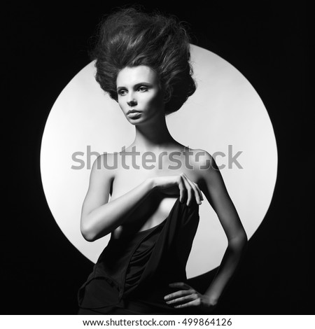 woman in black dress on black and white background. Sexy woman with beautiful body. Elegant woman with beautiful hairstyle. Shadows on beautiful body of sexy elegant woman. Professional female hairdo.