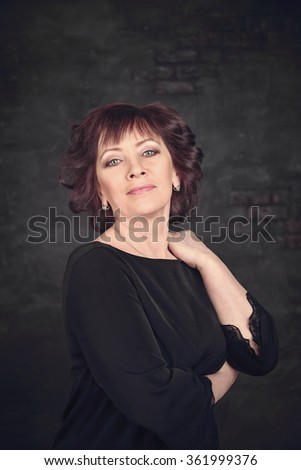 woman in black dress on gray background