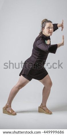 Woman in black dress pushing imaginary wall
