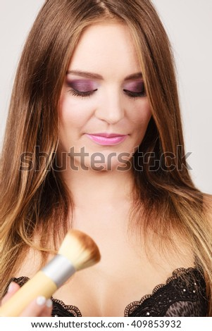 Woman in black lingerie applying anti-shine loose powder with brush to her body neckline. Pretty gorgeous girl beautifying. Fashion and makeup