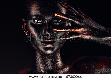 woman in black paint looking through fingers - stock photo