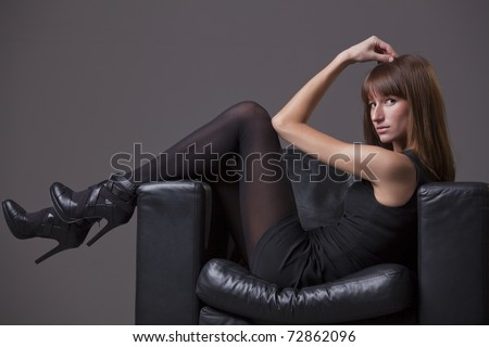 woman in black pantyhose and heels relaxing in chair - stock photo