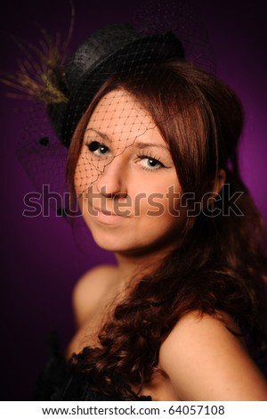 woman in black small hat against the violet background