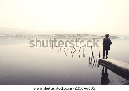Woman in black standing on jetty in a lake looking at the scenery. Edited image with vintage effect - stock photo