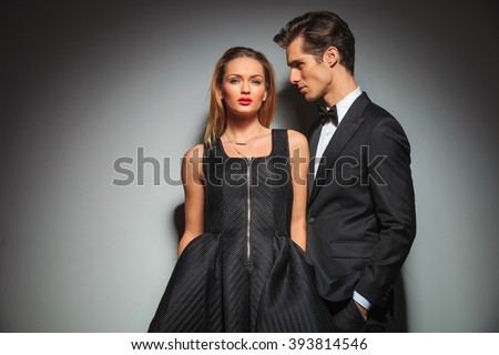 woman in black standing with hands in pockets and looking at the camera. businessman standing on woman's side with hands in pockets looking while posing in gray studio background.  - stock photo