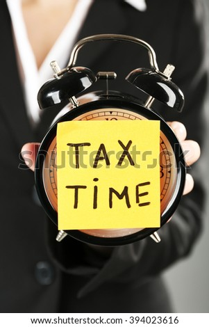 Woman in black suit holding alarm with tax time inscription, close up - stock photo