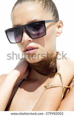 Woman in black sunglasses and swimsuit wearing golden bracelet with hair up poses on isolated white background. Fashion tan model. Beautiful awesome cool girl. Closeup portrait. Phuket, Thailand - stock photo