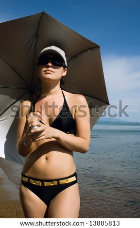 Woman in black swimsuit, cap and glasses under umbrella on the sea background