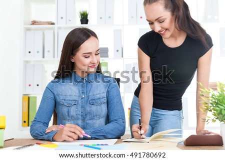 Woman in black T-shirt is writing her notebook. Her colleague in blue jeans shirt is looking at her. Concept of collaboration