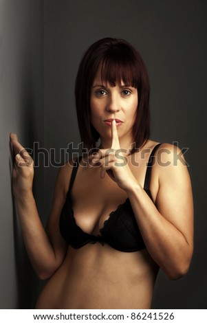 woman in black underwear looking sexy with finger up to mouth telling you to be  quiet - stock photo