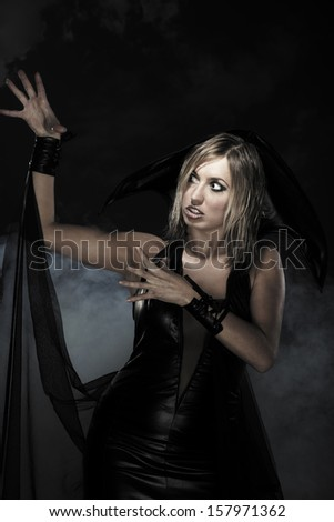 Woman in black witch dress for Halloween. Studio shot