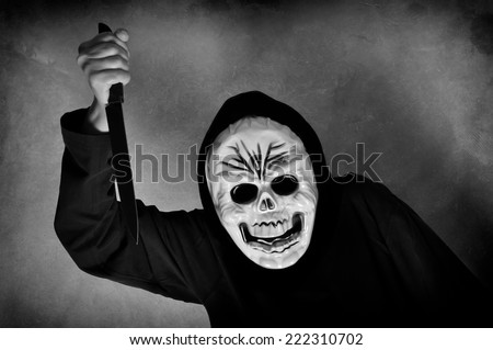 Woman in black with a plastic human skull mask holding a knife - stock photo
