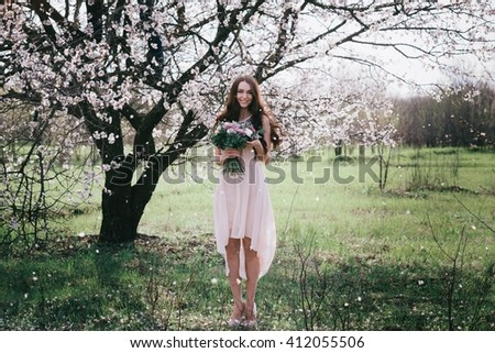 Woman in blooming trees. Woman with wedding bouquet in hands. Beautiful posing in a blooming apple garden.Spring mood. Young woman outdoors